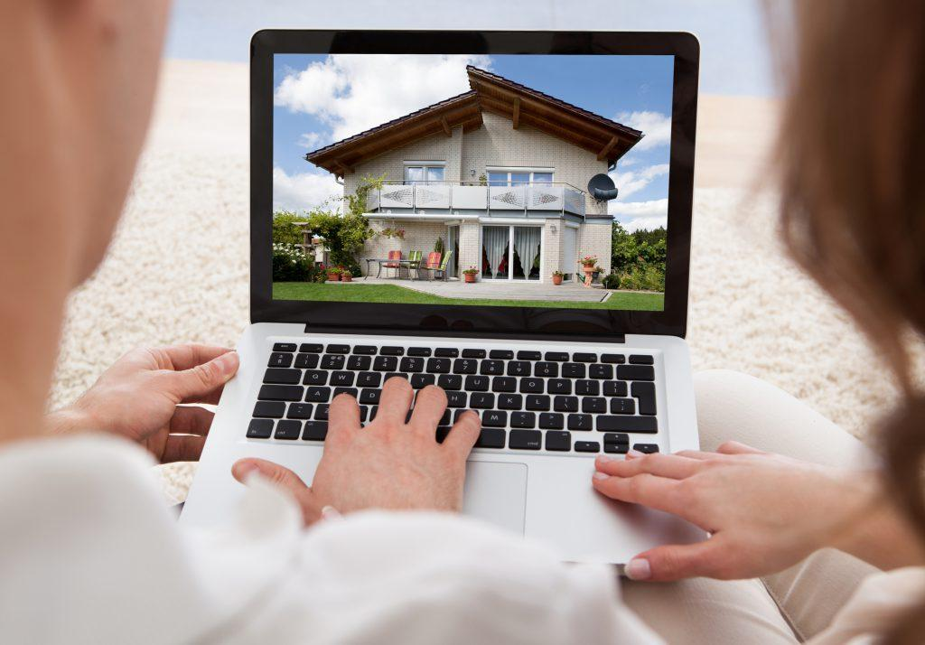 Couple Looking At House On Laptop's Screen